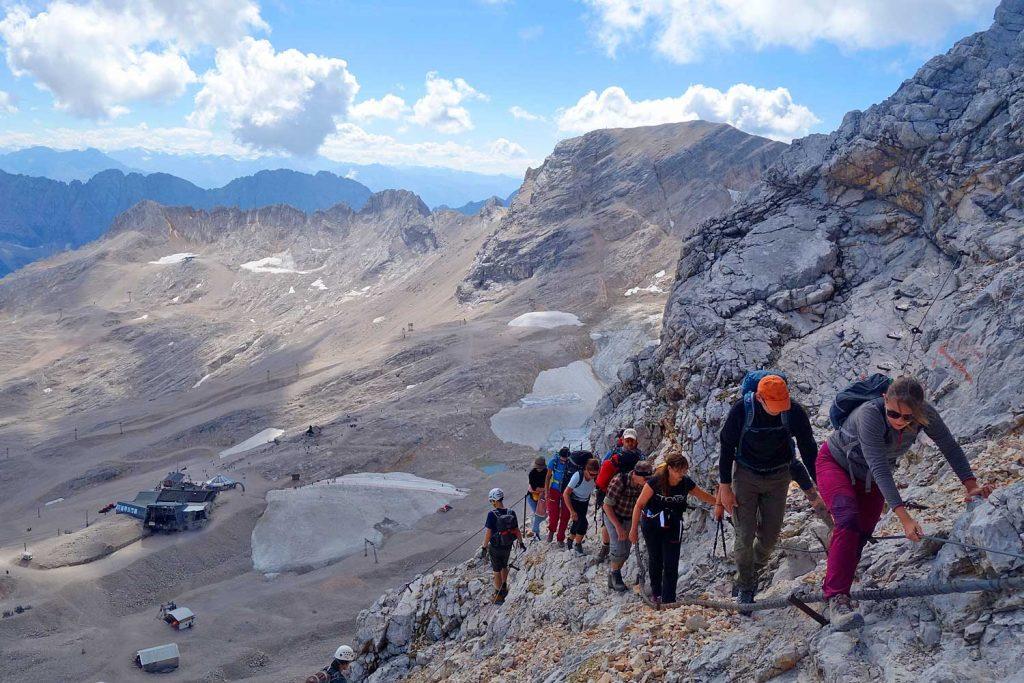Wanderung-durchs-Reintal-auf-die-Zugspitze---Bergsteiger-im-versicherten-Steig-mit-Blick-zum-Zugspitzplatt